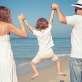 Ευτυχής οικογένεια που περπατά στην παραλία στο χρόνο ημέρας Στοκ Εικόνες