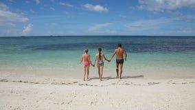 Ευτυχής οικογένεια που περπατά στη θάλασσα για να κολυμπήσει απόθεμα βίντεο