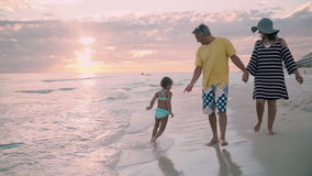 Ευτυχής οικογένεια που περπατά στο ωκεάνιο ηλιοβασίλεμα σκιαγραφιών ακτών απόθεμα βίντεο