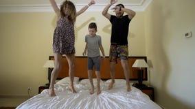 Ευτυχής οικογένεια που πηδά στο κρεβάτι r Άλμα πατέρων, μητέρων και μικρών παιδιών στο κρεβάτι απόθεμα βίντεο