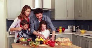 Ευτυχής οικογένεια που προετοιμάζει τα λαχανικά από κοινού απόθεμα βίντεο
