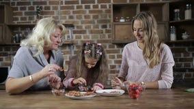 Ευτυχής οικογένεια που προετοιμάζει τα σπιτικά μπισκότα στην κουζίνα απόθεμα βίντεο