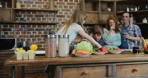 Ευτυχής οικογένεια που προετοιμάζει τα τρόφιμα στην κουζίνα, γονείς που εξετάζει τα παιδιά που κόβουν τα συστατικά για το νόστιμο απόθεμα βίντεο