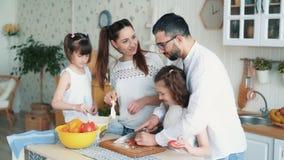 Ευτυχής οικογένεια που προετοιμάζει τα τρόφιμα στην κουζίνα, τέμνοντα λαχανικά, σε αργή κίνηση φιλμ μικρού μήκους