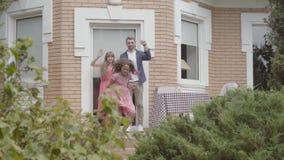 Ευτυχής οικογένεια που στέκεται στο μέρος από κοινού Φίλημα μητέρων και πατέρων αντίο σε λίγη κόρη και αυτή που αφήνει το σπίτι απόθεμα βίντεο