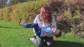 Ευτυχής οικογένεια που στηρίζεται στο χορτοτάπητα Η μητέρα με τα παιχνίδια τρυφερότητας και αγάπης με το παιδί της, ο γιος γελά,  απόθεμα βίντεο