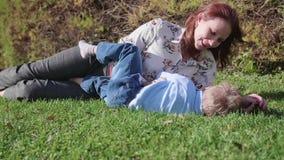 Ευτυχής οικογένεια που στηρίζεται στο χορτοτάπητα Η μητέρα με την τρυφερότητα και την αγάπη αγκαλιάζει το παιδί της, τα γέλια γιω φιλμ μικρού μήκους