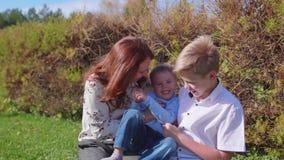 Ευτυχής οικογένεια που στηρίζεται στο χορτοτάπητα Παιχνίδια μητέρων με τα παιδιά της με την τρυφερότητα και την αγάπη, γελούν και απόθεμα βίντεο