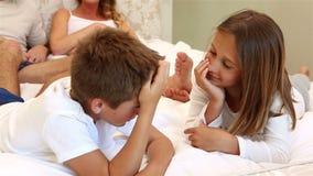 Ευτυχής οικογένεια που συζητά στο κρεβάτι απόθεμα βίντεο