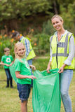 Ευτυχής οικογένεια που συλλέγει τα σκουπίδια στοκ εικόνα με δικαίωμα ελεύθερης χρήσης