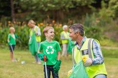 Ευτυχής οικογένεια που συλλέγει τα σκουπίδια στοκ φωτογραφίες με δικαίωμα ελεύθερης χρήσης