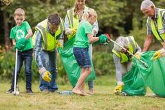 Ευτυχής οικογένεια που συλλέγει τα σκουπίδια στοκ εικόνες