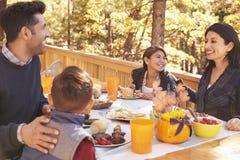 Ευτυχής οικογένεια που τρώει στον πίνακα σε μια γέφυρα σε ένα δάσος Στοκ φωτογραφία με δικαίωμα ελεύθερης χρήσης