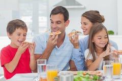 Ευτυχής οικογένεια που τρώει τις φέτες πιτσών στοκ εικόνες