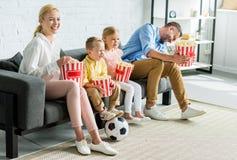 ευτυχής οικογένεια που τρώει popcorn καθμένος μαζί στον καναπέ στοκ εικόνες