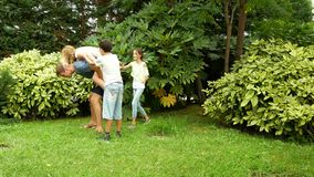 Ευτυχής οικογένεια που χορεύει μαζί στη χλόη σε ένα πάρκο με την όμορφη φύση 4K διάστημα αντιγράφων Τρόπος ζωής φιλμ μικρού μήκους