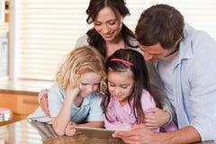 Ευτυχής οικογένεια που χρησιμοποιεί έναν υπολογιστή ταμπλετών από κοινού Στοκ εικόνα με δικαίωμα ελεύθερης χρήσης