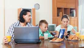 Ευτυχής οικογένεια που χρησιμοποιεί τις ηλεκτρονικές συσκευές Στοκ φωτογραφίες με δικαίωμα ελεύθερης χρήσης