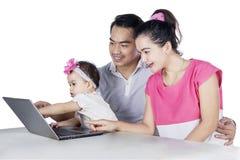 Ευτυχής οικογένεια που χρησιμοποιεί το lap-top από κοινού Στοκ Εικόνα
