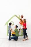 Ευτυχής οικογένεια που χρωματίζει το σπίτι τους από κοινού Στοκ εικόνα με δικαίωμα ελεύθερης χρήσης