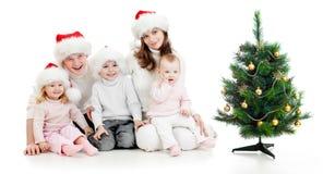 Ευτυχής οικογένεια στα καπέλα Santa με το χριστουγεννιάτικο δέντρο στοκ φωτογραφίες με δικαίωμα ελεύθερης χρήσης