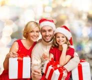 Ευτυχής οικογένεια στα καπέλα αρωγών santa με τα κιβώτια δώρων Στοκ Εικόνα