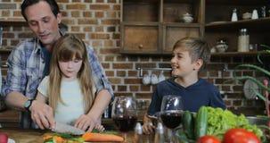 Ευτυχής οικογένεια στα τεμαχίζοντας λαχανικά μαγειρέματος, πατέρων και κορών κουζινών ενώ συνταγή ξεφυλλίσματος μητέρων σε Διαδίκ απόθεμα βίντεο