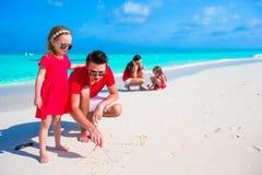 Ευτυχής οικογένεια στην άσπρη παραλία κατά τη διάρκεια των θερινών διακοπών Στοκ φωτογραφία με δικαίωμα ελεύθερης χρήσης