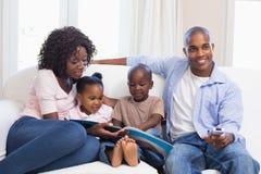 Ευτυχής οικογένεια στην ανάγνωση καναπέδων storybook Στοκ εικόνες με δικαίωμα ελεύθερης χρήσης