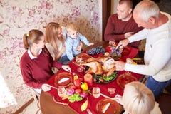 Ευτυχής οικογένεια στην ημέρα των ευχαριστιών επιτραπέζιου εορτασμού γευμάτων σε ένα θολωμένο υπόβαθρο Παραδοσιακή έννοια ημέρας  Στοκ Εικόνες