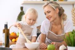 Ευτυχής οικογένεια στην κουζίνα Κόρη μητέρων και παιδιών που μαγειρεύει νόστιμο πιό breakfest Στοκ Εικόνες