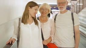 Ευτυχής οικογένεια στην κυλιόμενη σκάλα στη λεωφόρο αγορών Ανώτερο ζεύγος και η κόρη τους που κουβεντιάζουν και που γελούν απόθεμα βίντεο