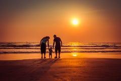 ευτυχής οικογένεια στην παραλία ηλιοβασιλέματος στην παραλία Arambol, ο Βορράς Goa, Ινδία Στοκ Φωτογραφία