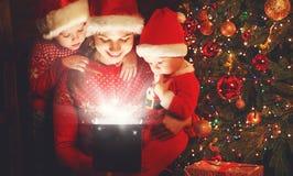 Ευτυχής οικογένεια στη Παραμονή Χριστουγέννων η μητέρα και τα παιδιά ανακαλύπτουν ένα μΑ στοκ εικόνα