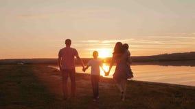 Ευτυχής οικογένεια στη σκιαγραφία ηλιοβασιλέματος Στοκ Φωτογραφία