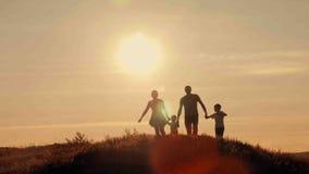 Ευτυχής οικογένεια στη σκιαγραφία ηλιοβασιλέματος Στοκ φωτογραφίες με δικαίωμα ελεύθερης χρήσης