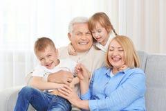 Ευτυχής οικογένεια στον καναπέ στοκ εικόνα με δικαίωμα ελεύθερης χρήσης