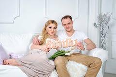 Ευτυχής οικογένεια στο άσπρο καθιστικό Άνδρας και γυναίκα Στοκ Εικόνες
