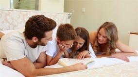 Ευτυχής οικογένεια στο βιβλίο ανάγνωσης κρεβατιών απόθεμα βίντεο