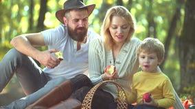 Ευτυχής οικογένεια στο ηλιόλουστο πάρκο Ευτυχές χόμπι από κοινού Οικογένεια που τρώει το φρέσκο μήλο Υγιής και ευτυχής χρόνος με  απόθεμα βίντεο