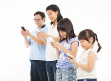 Ευτυχής οικογένεια σχετικά με το έξυπνο τηλέφωνο στοκ εικόνες