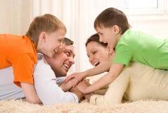 Ευτυχής οικογένεια τέσσερα σε ένα φως Στοκ Εικόνες