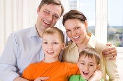 Ευτυχής οικογένεια τέσσερα σε ένα φως Στοκ εικόνα με δικαίωμα ελεύθερης χρήσης