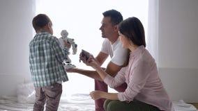 Ευτυχής οικογένεια της μητέρας και του πατέρα που παρουσιάζουν ένα ρομπότ αιφνιδιαστικών παιχνιδιών στο γιο στο σπίτι, καινοτόμο  απόθεμα βίντεο