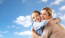 Ευτυχής οικογένεια του κοριτσιού και της μητέρας που αγκαλιάζουν πέρα από τον ουρανό Στοκ Εικόνα