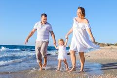 Ευτυχής οικογένεια τριών - έγκυα χέρια εκμετάλλευσης μητέρων, πατέρων και κορών και κατοχή της διασκέδασης που περπατά στην παραλ Στοκ Εικόνα