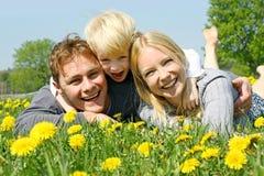 Ευτυχής οικογένεια τριών ανθρώπων που χαλαρώνουν στο λιβάδι λουλουδιών Στοκ Φωτογραφίες