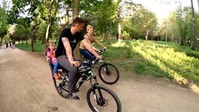 Ευτυχής οικογένεια τριών οδηγώντας ποδηλάτων σε πράσινο απόθεμα βίντεο