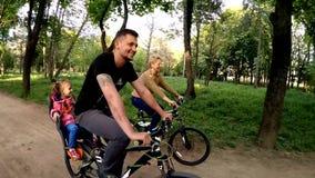 Ευτυχής οικογένεια τριών οδηγώντας ποδηλάτων σε πράσινο φιλμ μικρού μήκους