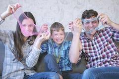 Ευτυχής οικογένεια mom, γιος και μπαμπάς και παιχνίδι με slimes που κάθονται στον καναπέ Τέντωμα slime Κοίταγμα μέσω στοκ φωτογραφία με δικαίωμα ελεύθερης χρήσης